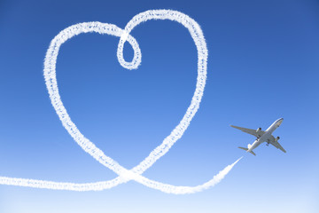 Airplane flying with the heart shape in the sky