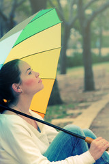 Young woman looks at the sun under a big rainbow umbrella