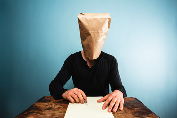 Man with bag over head writing letter