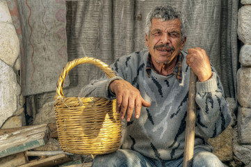 Senior farmer holding a basket and resting