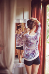 Young woman at home near the mirror