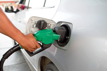 close up of man hand putting gas into the car at gas station