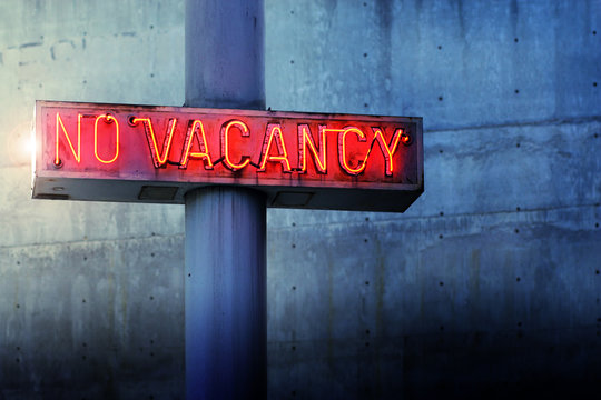 Glowing retro neon 'no vacancy' sign against blue wall