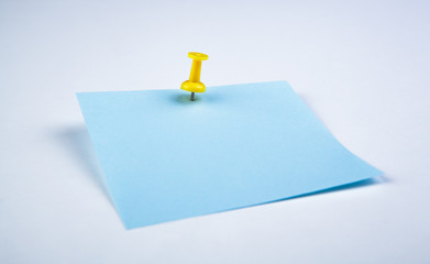 sheet of blue paper witn push pin