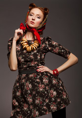 Girl in Russian style posing in red kerchief and bagels on the n