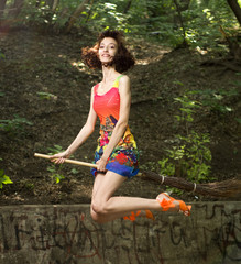 Beautiful young girl on broomstick
