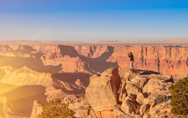 Adventurous man taking a photo at Grand Canyon before sunset