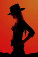 Silhouette of cowgirl with hands on her hips