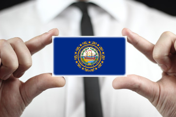 Businessman holding New Hampshire State Flag