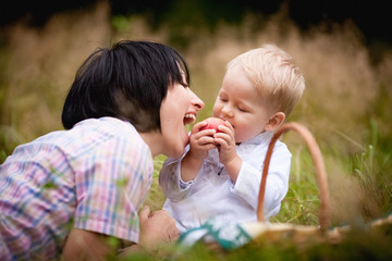 Mom and son eating fruit with wicker baskets