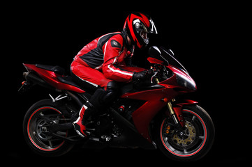 Motorcyclist in red equipment on black background Wall mural