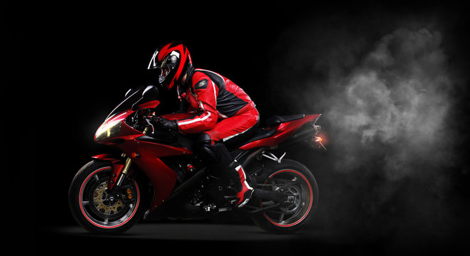 Motorcyclist in red equipment  side view full length