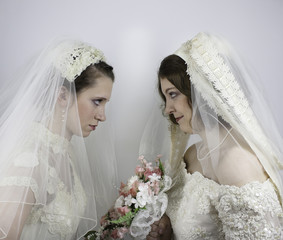 Two young brides staring at each other like bridezillas