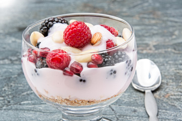 Glass of creamy rich berry parfait with almonds