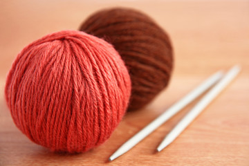 Wool and knitting needles closeup on wooden background.