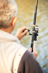 Foto op Canvas Jacht Senior Fisherman holding Fishing Rod with Reel.