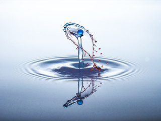 Blue water drop hits red liquid