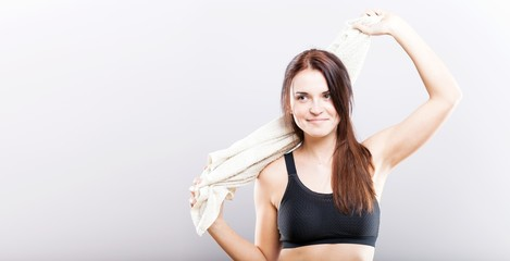 Young woman after fitness exercise wiping with towel