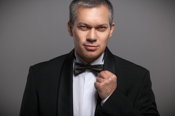 Closeup portrait of sexy man in black suit and bow tie