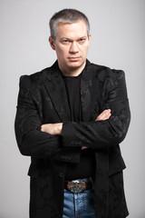 portrait of adult man in black jacket holding hands crossed