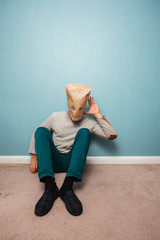 Man with bag over head on floor is listening