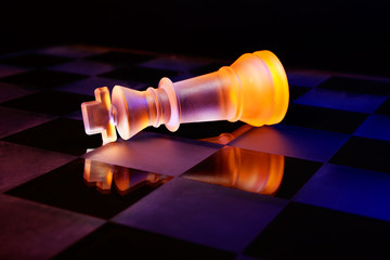 Glass chess on a chess board lit by blue and orange light