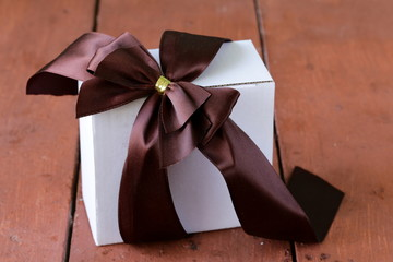 white gift box with ribbon bow on a wooden background