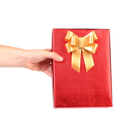 Red gift box with golden bow in hand.