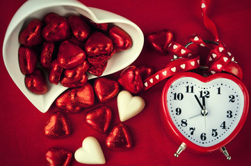 Red heart shaped clock with sweet chocolates