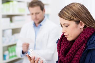 kundin in der apotheke schaut auf medikament