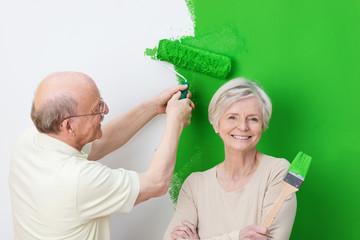fröhliches älteres paar streicht grün an