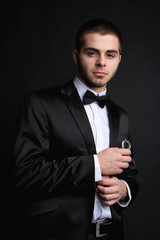 Handsome young man in suit holding watch on dark background