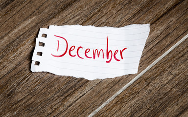 December written on the paper on a wood background