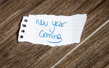 New Year Coming written on the paper on a wood background