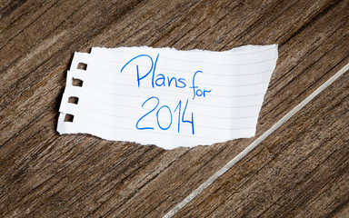 Plans for 2014 written on the paper on a wood background