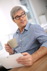 Businessman relaxing in office with tablet and coffee cup