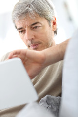 Mature man in sofa websurfing with tablet