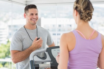 Trainer helping woman on treadmill
