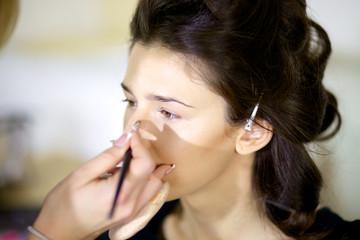 Beautiful model getting makeup