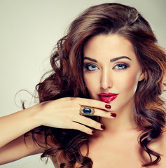 Model brunette  with beautiful curly  hair . Girl with wavy hair hairstyle and with a ring on her hand