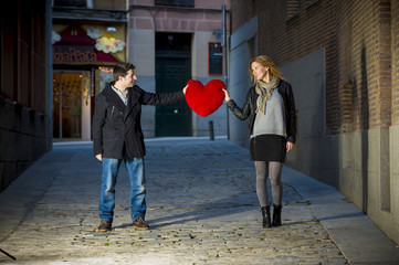 couple smiling at each other holding a red heart