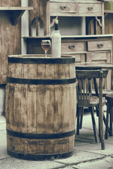 Vintage stylized photo of wooden barrel with bottles of wine and
