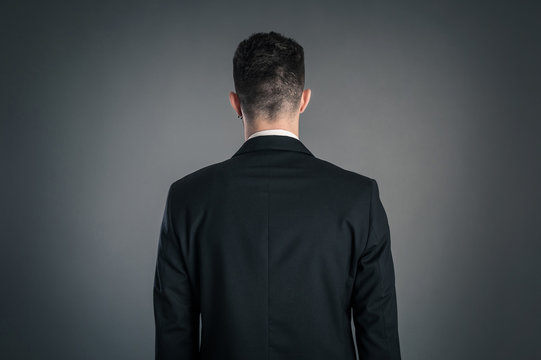 Portrait of a businessman back view isolated on dark background.