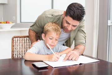 Happy father helping son with math homework at table