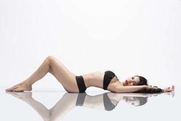Beautiful Asian Girl laying on reflective surface
