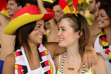 German girls friends soccer fans celebrating.