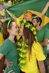 Brazilian girlfriends soccer fans almost kissing each other.