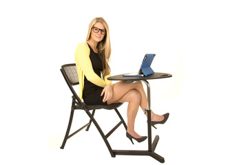 pretty blonde with glasses sitting at desk with legs crossed