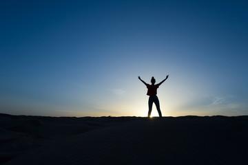 Silhouette de femme debout, soleil couchant