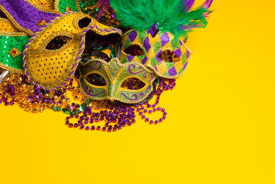 group of Mardi Gras or venetian mask sor costumes on a yellow